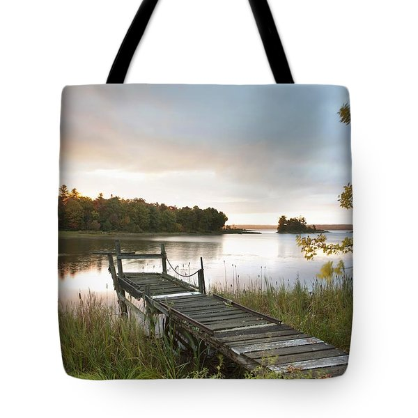 Tote Bag featuring the photograph A Dock On A Lake At Sunrise Near Wawa by Susan Dykstra