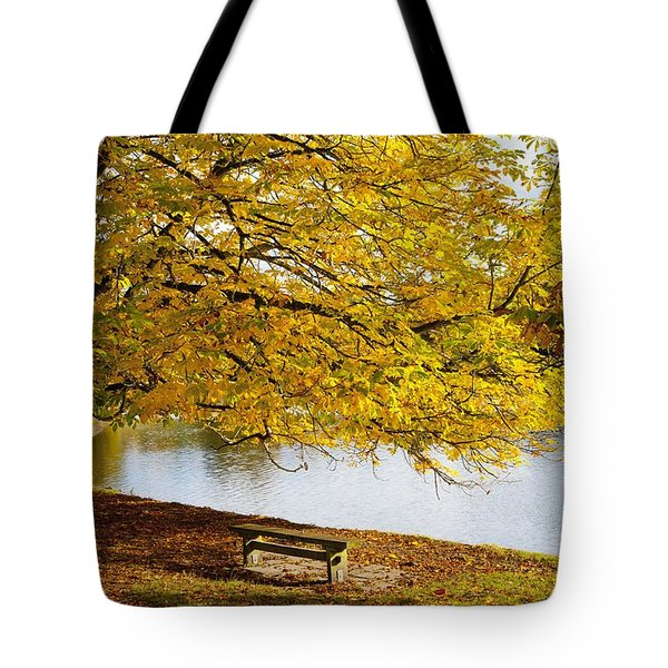 A Large Tree And Bench Along The Water Tote Bag by John Short