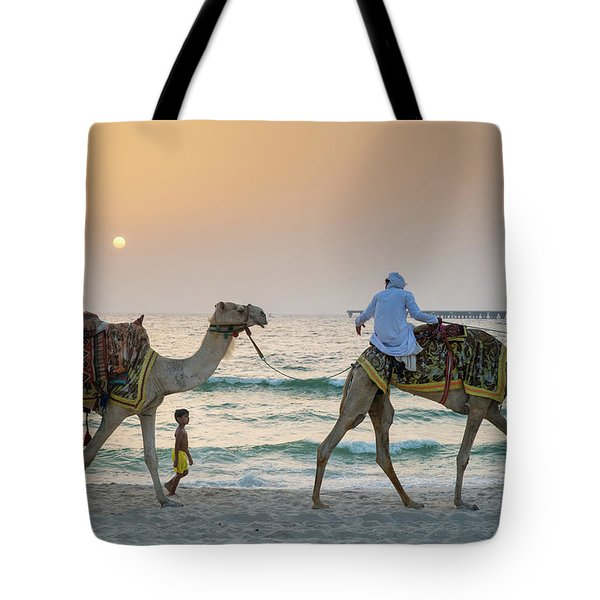 A Little Boy Stares In Amazement At A Camel Riding On Marina Beach In Dubai, United Arab Emirates Tote Bag