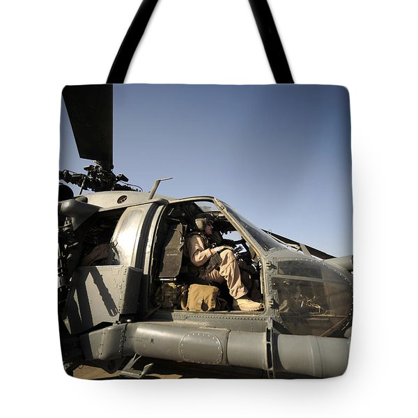 A Pilot Sits In The Cockpit Of A Hh-60g Tote Bag by Stocktrek Images