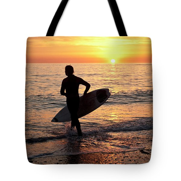 A Young Man Surfing At Sunset Off Aberystwyth Beach, Wales Uk Tote Bag