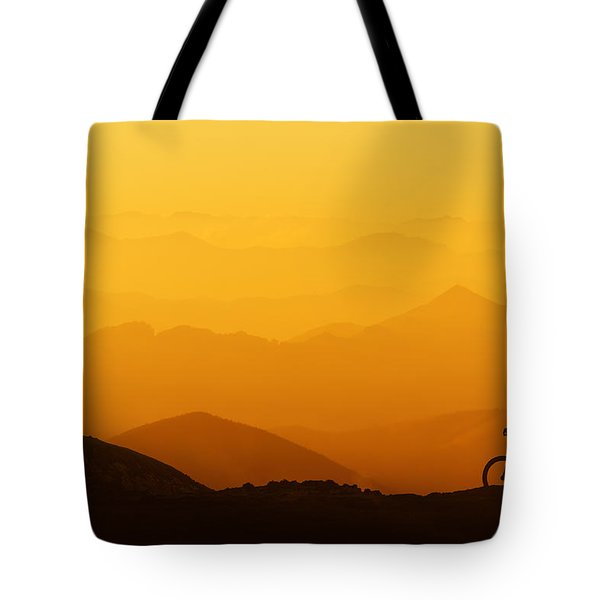 Biker Riding On Mountain Silhouettes Background Tote Bag