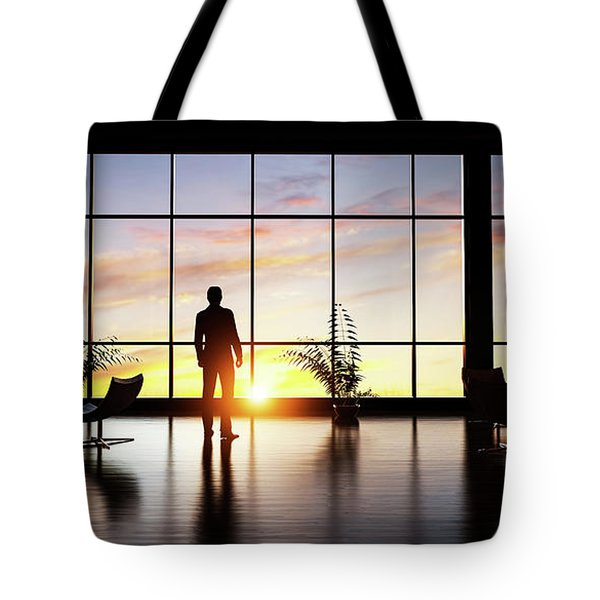 Business Man Standing In The Office Looking Out Of The Window At Sunset Sky. Tote Bag
