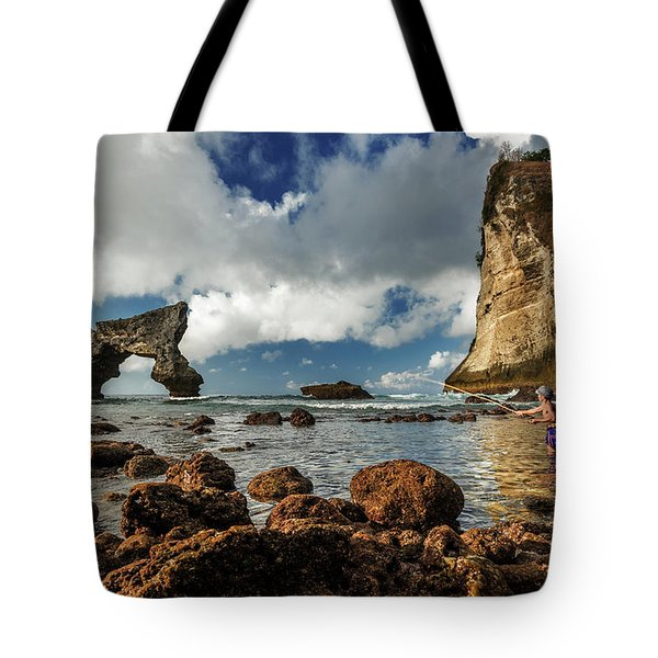Tote Bag featuring the photograph catching fish in Atuh beach by Pradeep Raja Prints