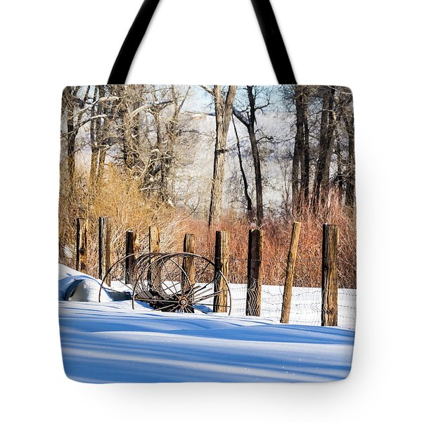 Tote Bag featuring the photograph Colorado Winter Snow Scene With Old Farming Rake And Rustic Fence by Nadja Rider