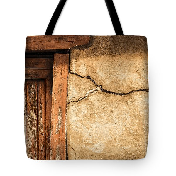 Tote Bag featuring the photograph Cracked Lime Stone Wall And Detail Of An Old Wooden Door by Semmick Photo