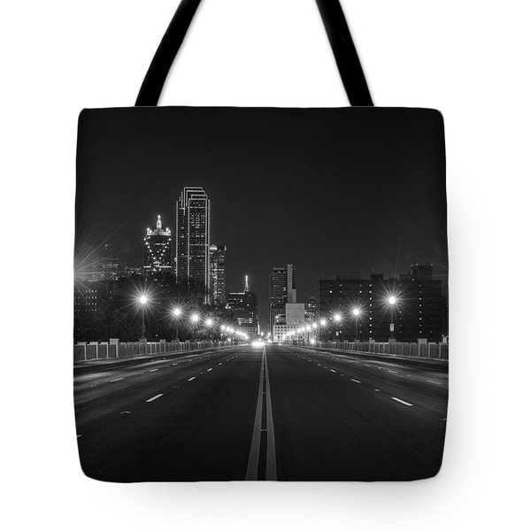 Tote Bag featuring the photograph Crossing The Bridge To Downtown Dallas At Night In Black And White by Todd Aaron