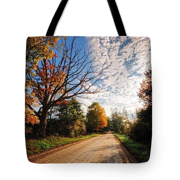 Tote Bag featuring the photograph Dirt Road And Sky In Fall by Lars Lentz