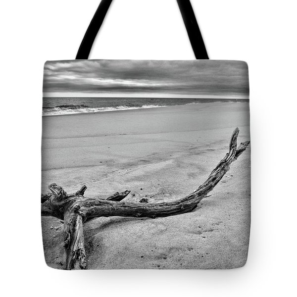 Tote Bag featuring the photograph Driftwood On The Beach In Black And White by Paul Ward