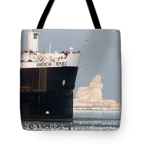 Great Lakes Ship Passing A Frozen Cleveland Lighthouse Tote Bag