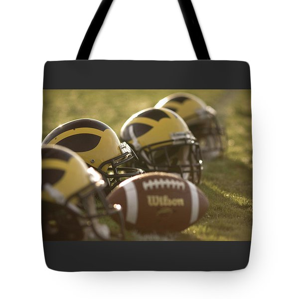 Helmets And A Football On The Field At Dawn Tote Bag