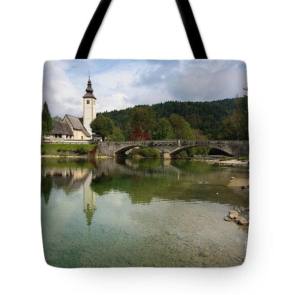 Tote Bag featuring the photograph Lake Bohinj With Church In Slovenia by IPics Photography