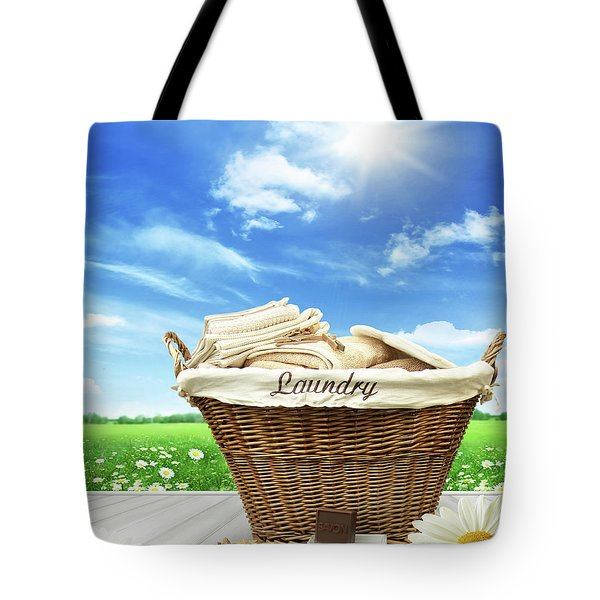 Laundry Basket With Clothes On Rustic Table Against Blue Sky Tote Bag