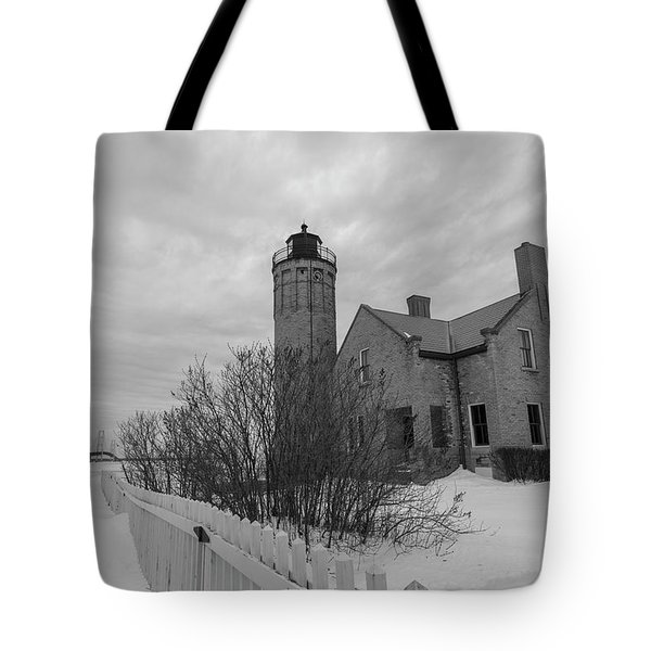 Tote Bag featuring the photograph Lighthouse And Mackinac Bridge Winter Black And White  by John McGraw