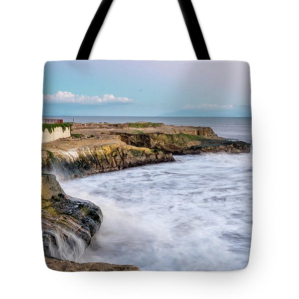 Long Exposure Of Waves Against The Cliff With Lighthouse In Shot Tote Bag