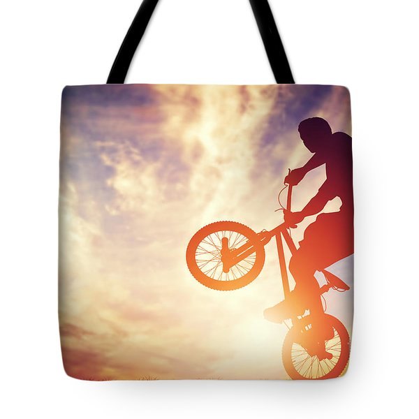 Man Riding A Bmx Bike Performing A Trick Against Sunset Sky Tote Bag by Michal Bednarek
