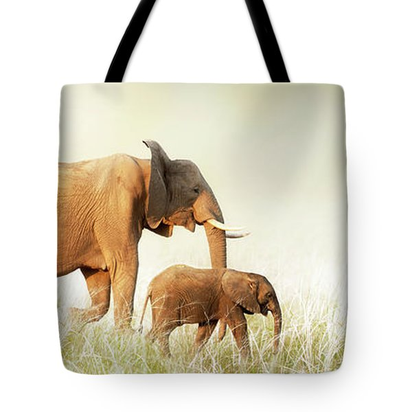 Mom And Baby Elephant Walking Through Tall Grass Tote Bag