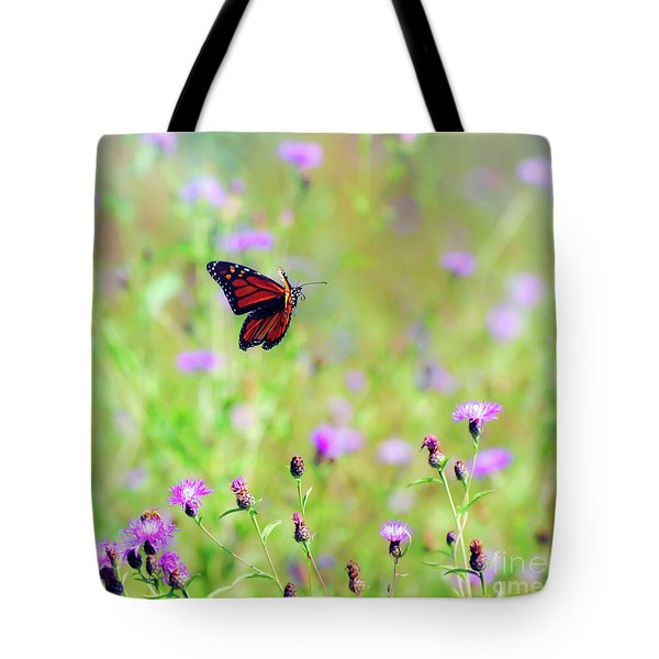 Tote Bag featuring the photograph Monarch Butterfly In Flight Over The Wildflowers by Kerri Farley