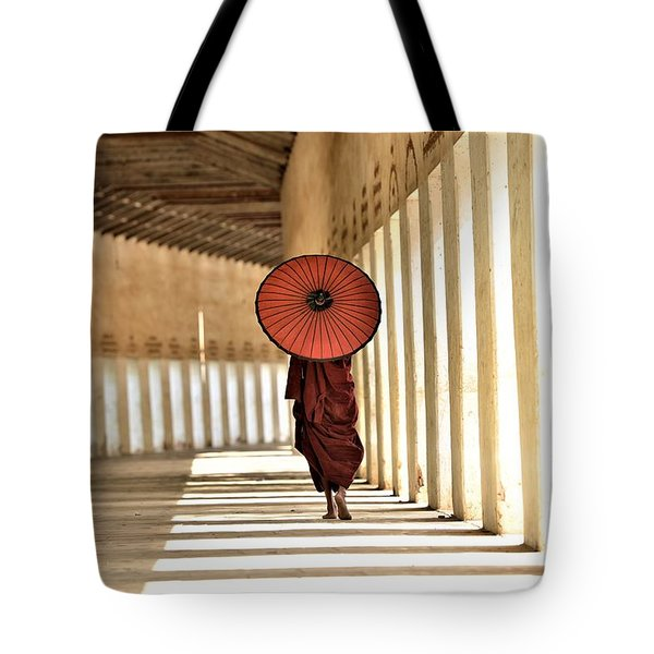 Monk With Umbrella Walking In Th Light Passway Tote Bag