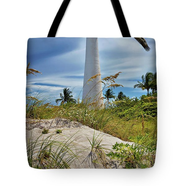 Tote Bag featuring the photograph Pelican Flying Over Cape Florida Lighthouse by Justin Kelefas