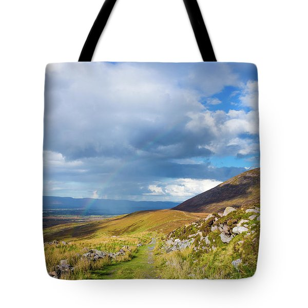 Tote Bag featuring the photograph Raining Down And Sunshine With Rainbow On The Countryside In Ire by Semmick Photo