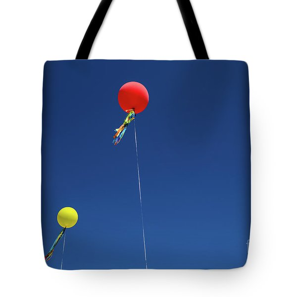 Tote Bag featuring the photograph Red,yellow Balloon Blowing By The Wind In The Air With The Blue  by Jingjits Photography