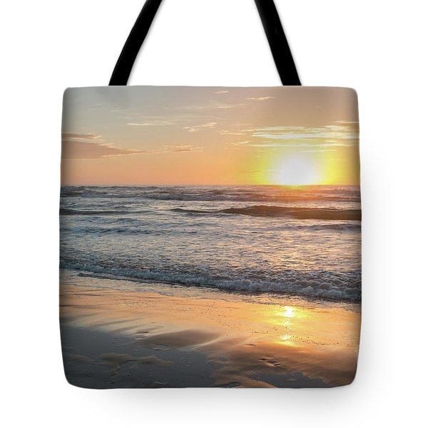 Rising Sun Reflecting On Wet Sand With Calm Ocean Waves In The B Tote Bag