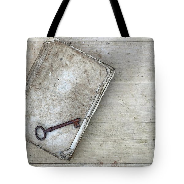 Tote Bag featuring the photograph Rusty Key On The Old Tattered Book by Michal Boubin