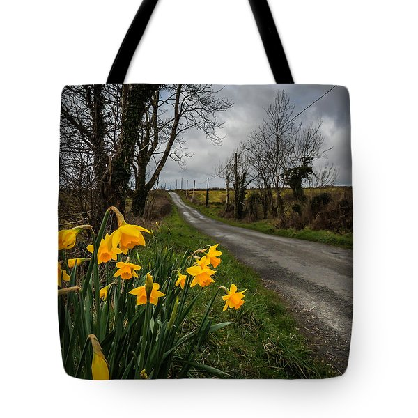 Tote Bag featuring the photograph Spring Daffodils On An Irish Country Road by James Truett