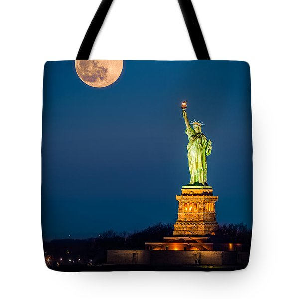 Tote Bag featuring the photograph Statue Of Liberty And A Rising Supermoon In New York City by Mihai Andritoiu