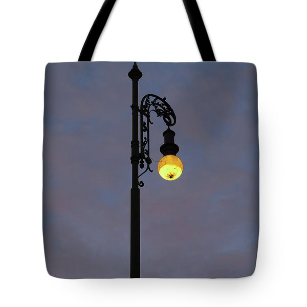Tote Bag featuring the photograph Street Lamp Shining At Dusk by Michal Boubin