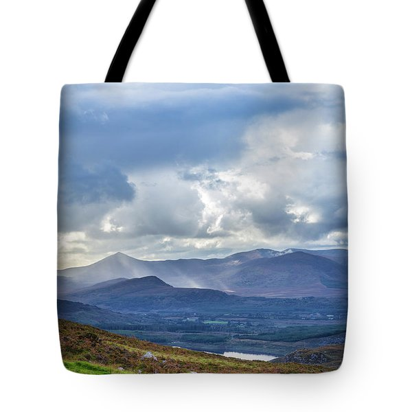 Tote Bag featuring the photograph Sun Rays Piercing Through The Clouds Touching The Irish Landscap by Semmick Photo