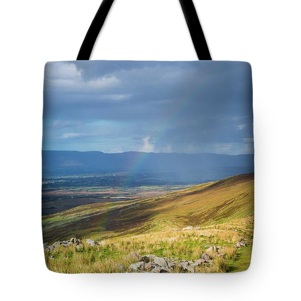 Tote Bag featuring the photograph Sunshine And Raining Down With Rainbow On The Countryside In Ire by Semmick Photo