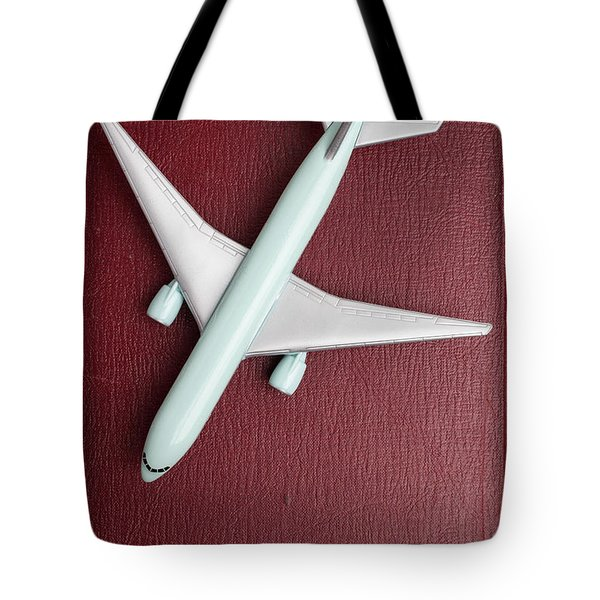 Tote Bag featuring the photograph Toy Airplane Over Red Book Cover by Edward Fielding