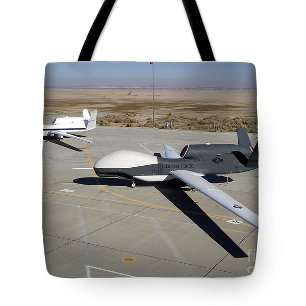 Two Global Hawks Parked On A Ramp Tote Bag by Stocktrek Images