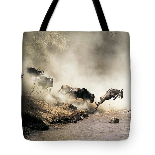 Wildebeest Leaping In Mid-air Over Mara River Tote Bag