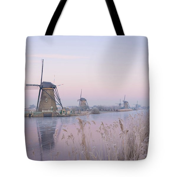 Tote Bag featuring the photograph Windmills In The Netherlands In The Soft Sunrise Light In Winter by IPics Photography