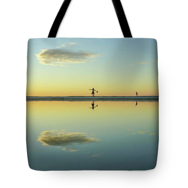 Woman And Cloud Reflected On Beach Lagoon At Sunset Tote Bag