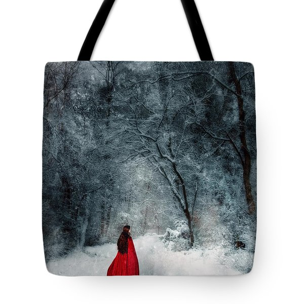 Woman In Red Cape Walking In Snowy Woods Tote Bag by Jill Battaglia