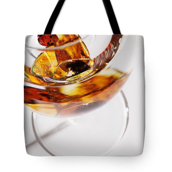 Tote Bag featuring the photograph Yellow Amber Stones In A Glass. by Andrey  Godyaykin