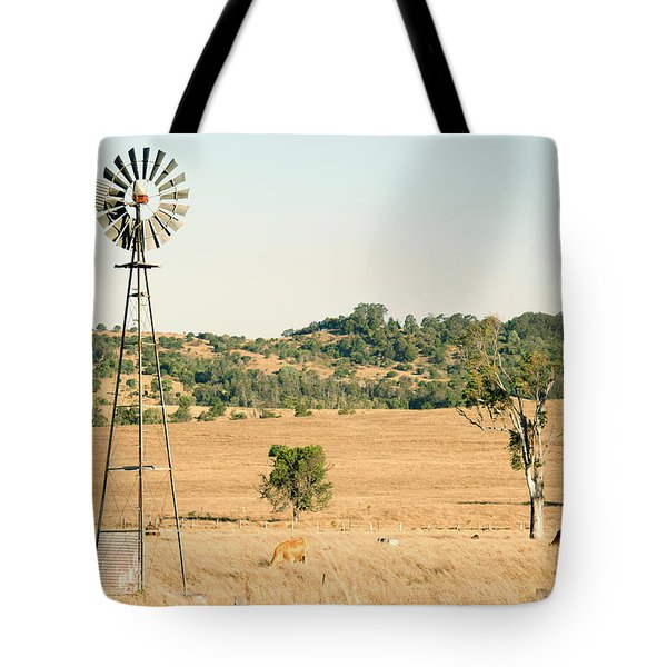 Tote Bag featuring the photograph Cows And A Windmill In The Countryside. by Rob D Imagery