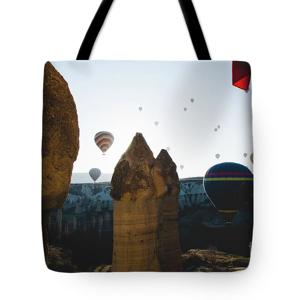 hot air balloons for tourists flying over rock formations at sunrise in the valley of Cappadocia. Tote Bag