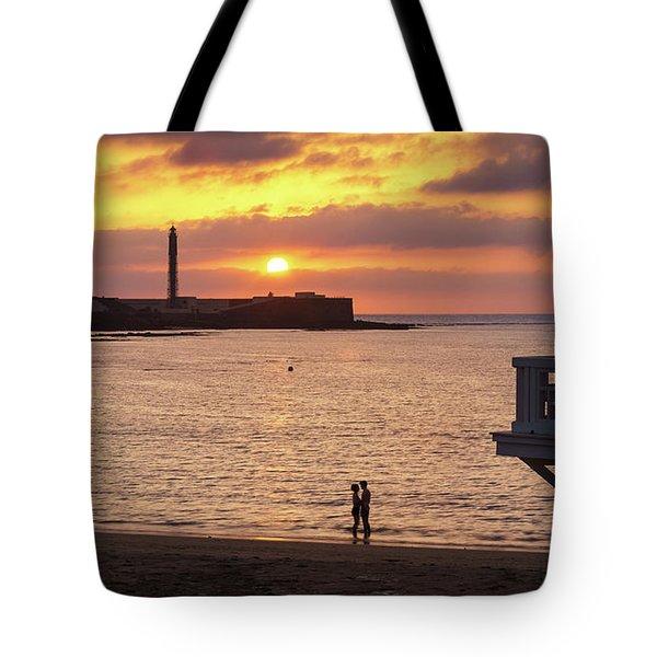 Tote Bag featuring the photograph Couple At Sunset In La Caleta Cadiz Spain by Pablo Avanzini