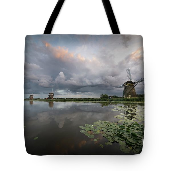 Tote Bag featuring the photograph Dramatic Sky Over Three Windmills In Holland by IPics Photography