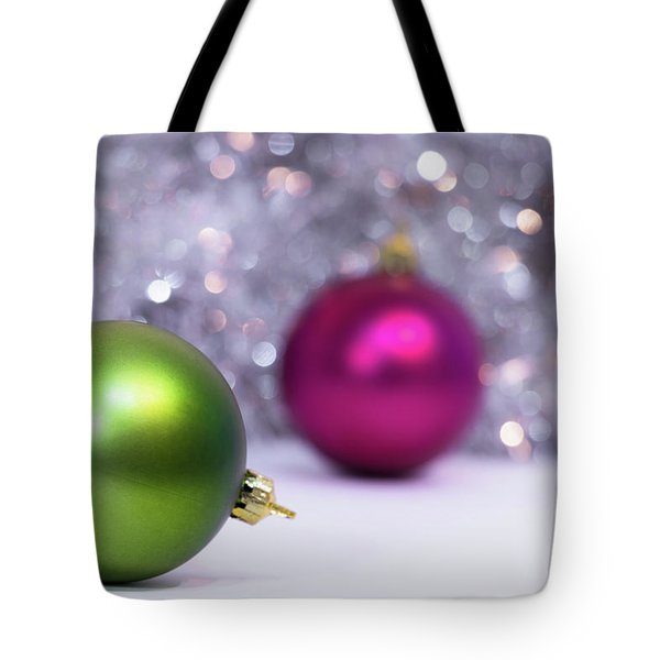 Tote Bag featuring the photograph Green And Fuchsia Christmas Balls And Lights In Background. Wint by Cristina Stefan