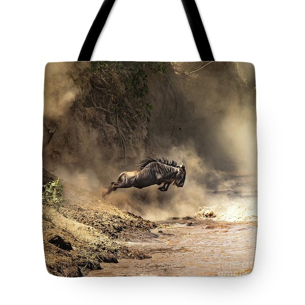 Wildebeest Leaps From The Bank Of The Mara River Tote Bag