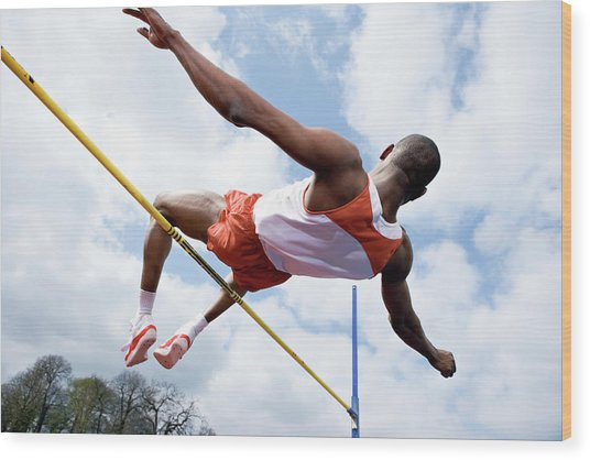 Athlete Performing A High Jump Wood Print by Gustoimages/science Photo Library