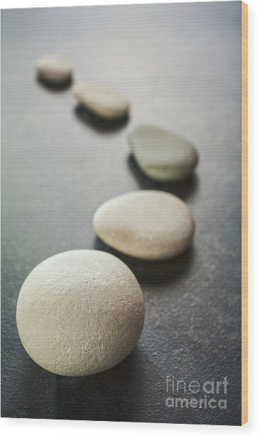 Curving Line Of Grey Pebbles On Dark Background Wood Print