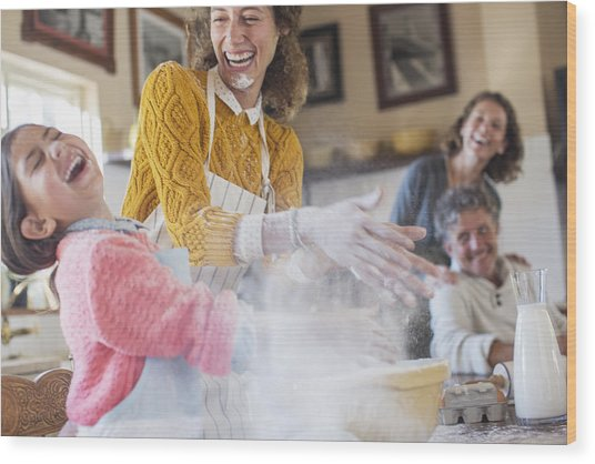 Mother And Daughter Playing With Flour In The Kitchen Wood Print by Caiaimage/Sam Edwards
