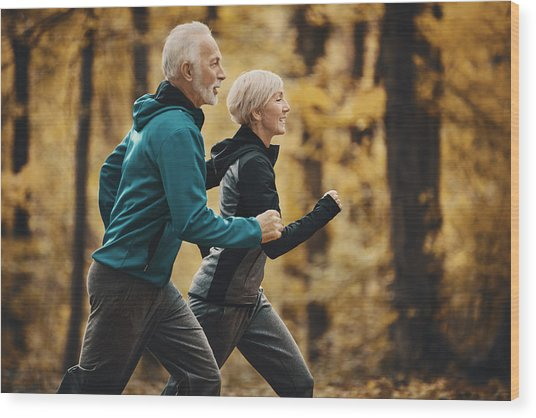 Senior Couple Jogging In A Forest. Wood Print by Gilaxia